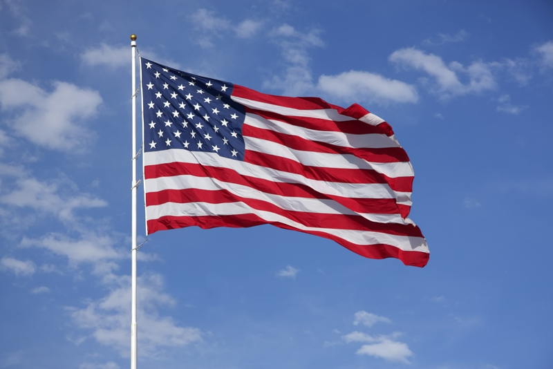 Full American Flag flying in the wind, with blue sky and clouds behind it